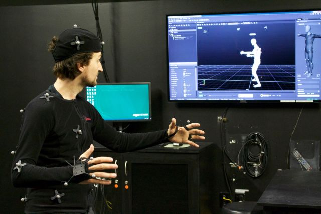 A man in a morph suit watches the movements he makes on a screen.