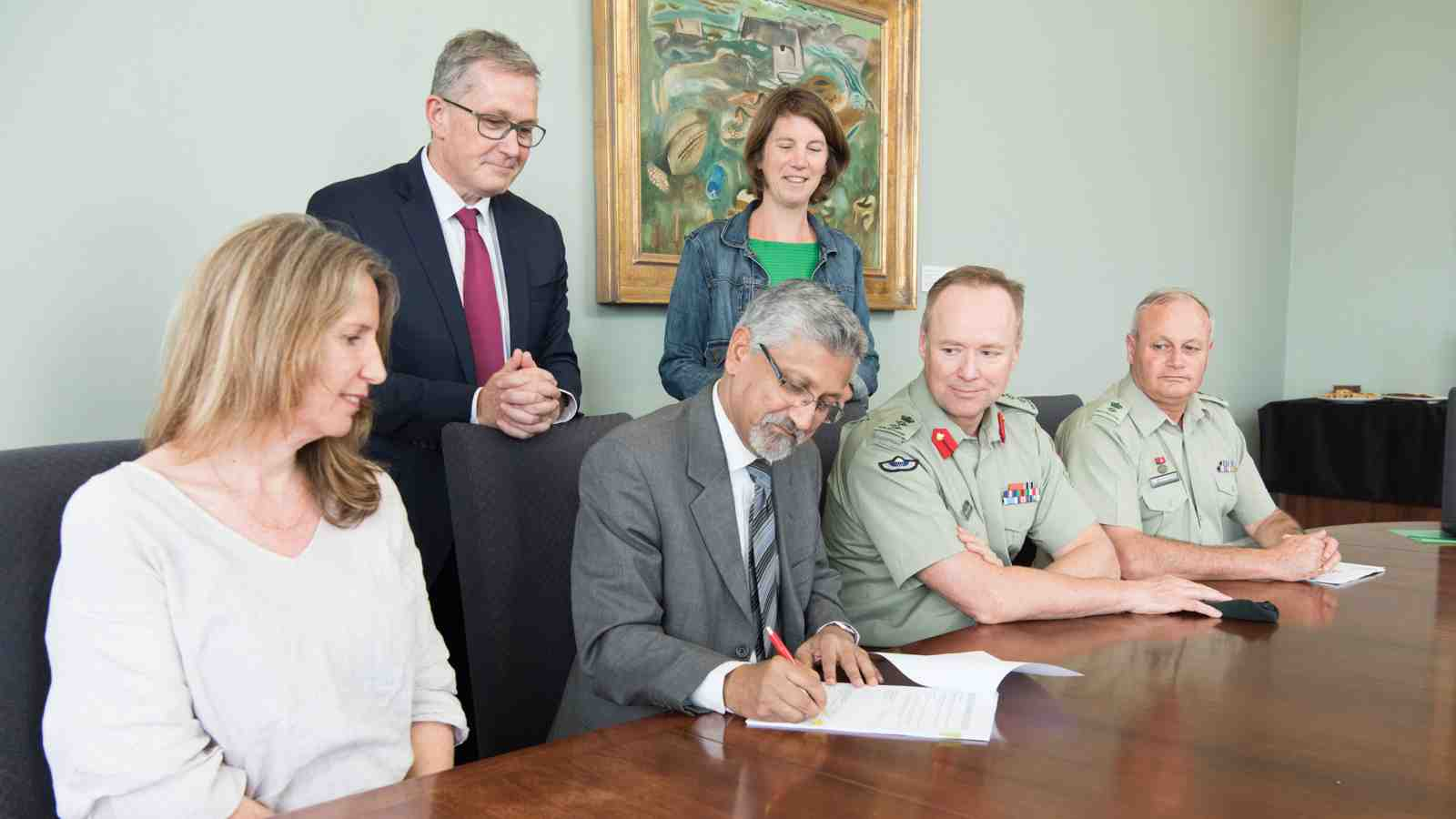 Victoria staff and Defence force staff at a table. A person in the middle is signing a document.