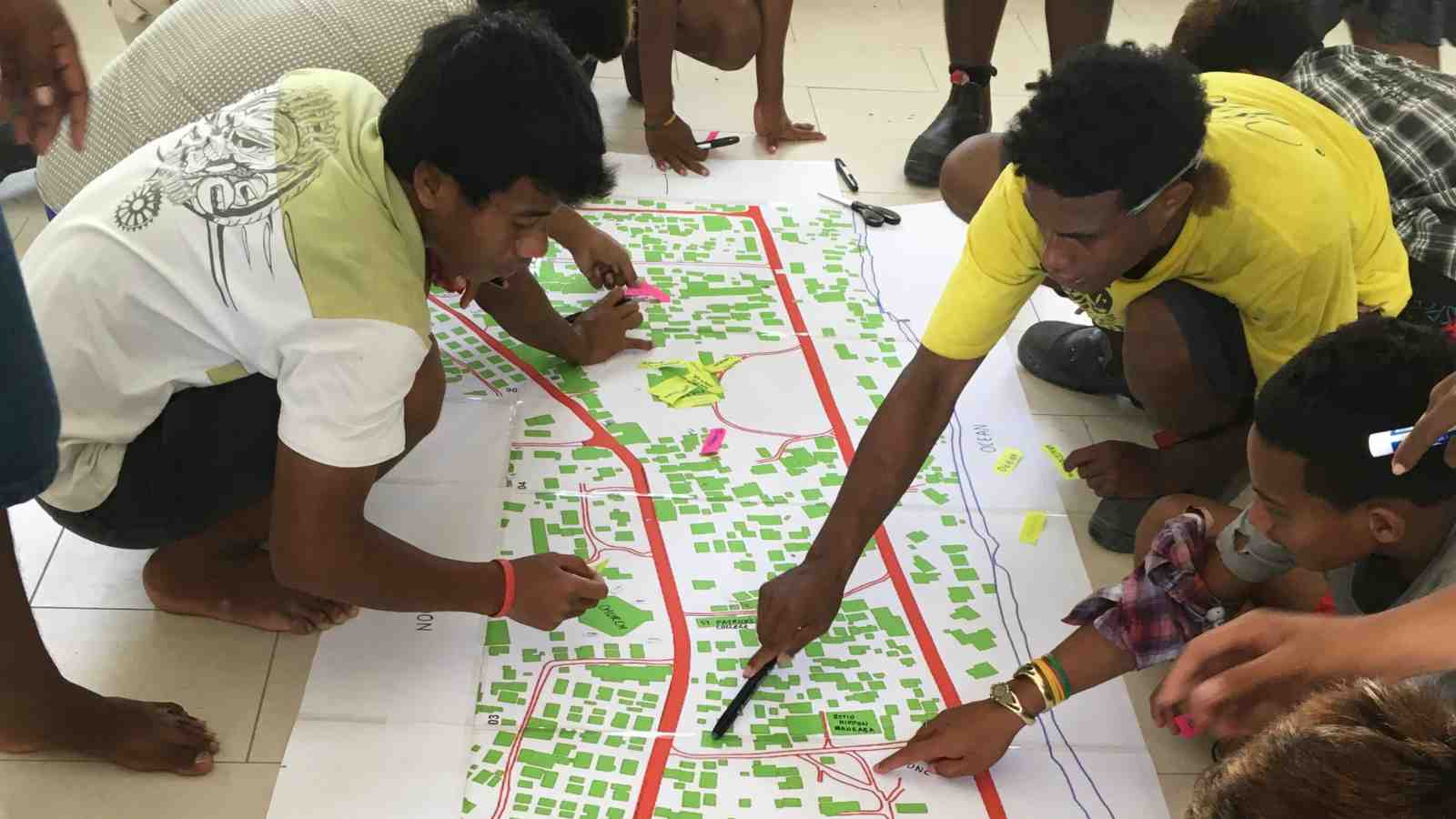 Members of Betio Youth, Kiribati, sit around an architectural drawing of their city, planning their new community centre.