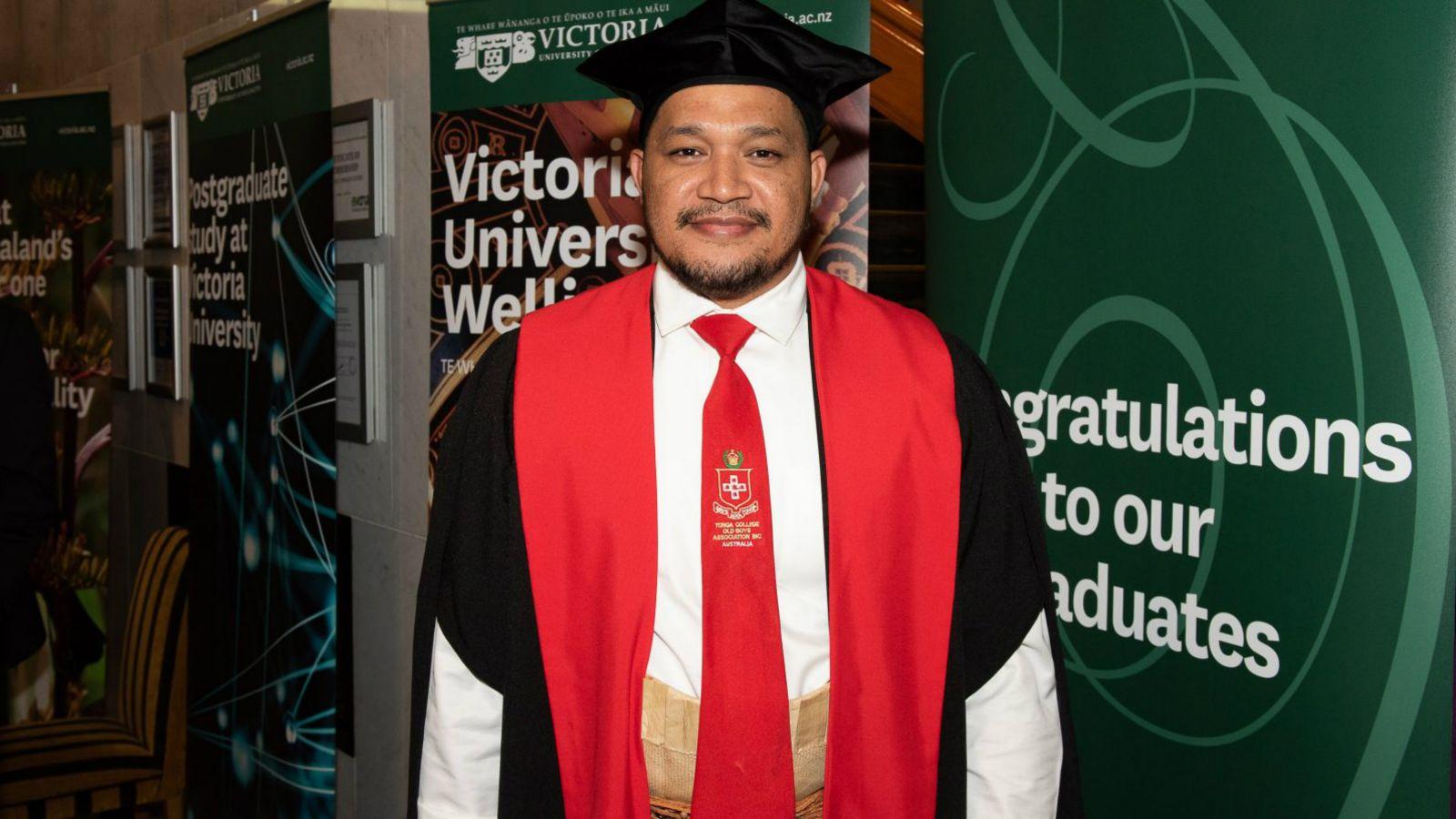 PhD graduate Taitusi Taufa, in graduation attire, stands in front of Victoria University of Wellington graduation banners