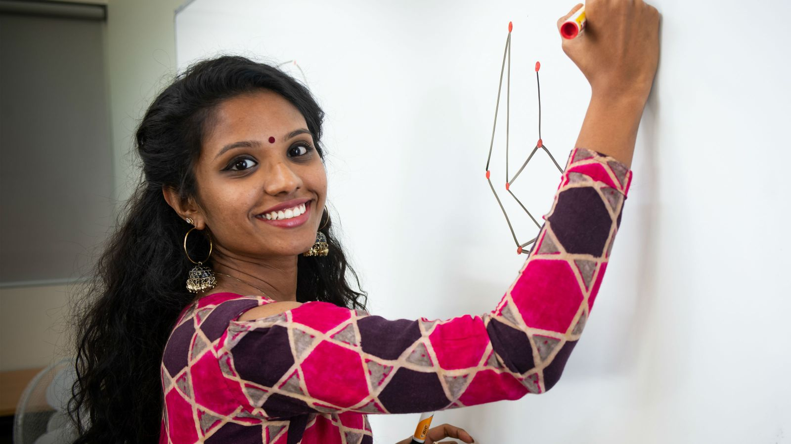 Meenu Jose draws images on a whiteboard.