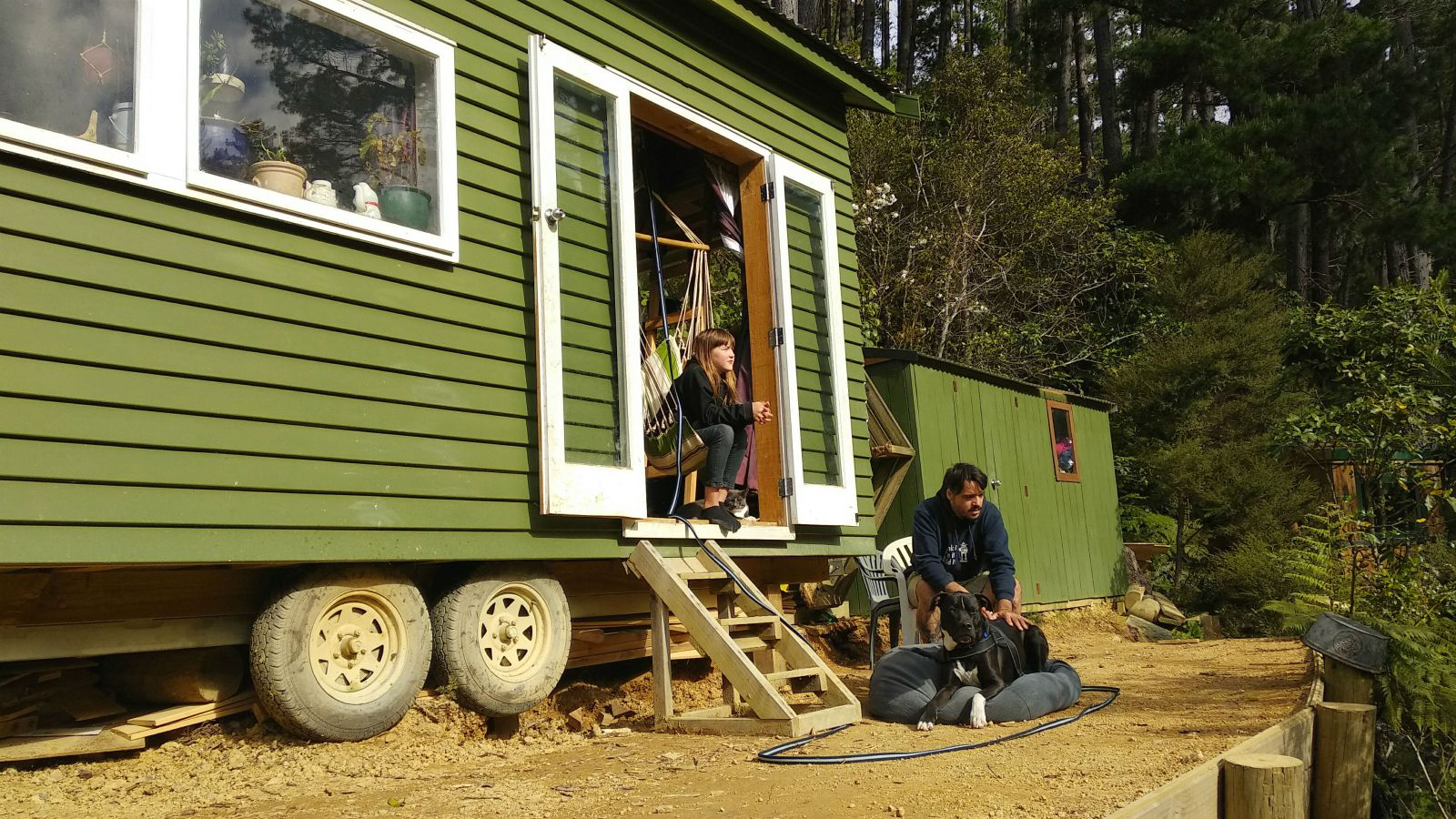 Daniel Burmester and his daughter, Charlee, outside their tiny house. The house is green with white doors and wooden steps leading up to the door.