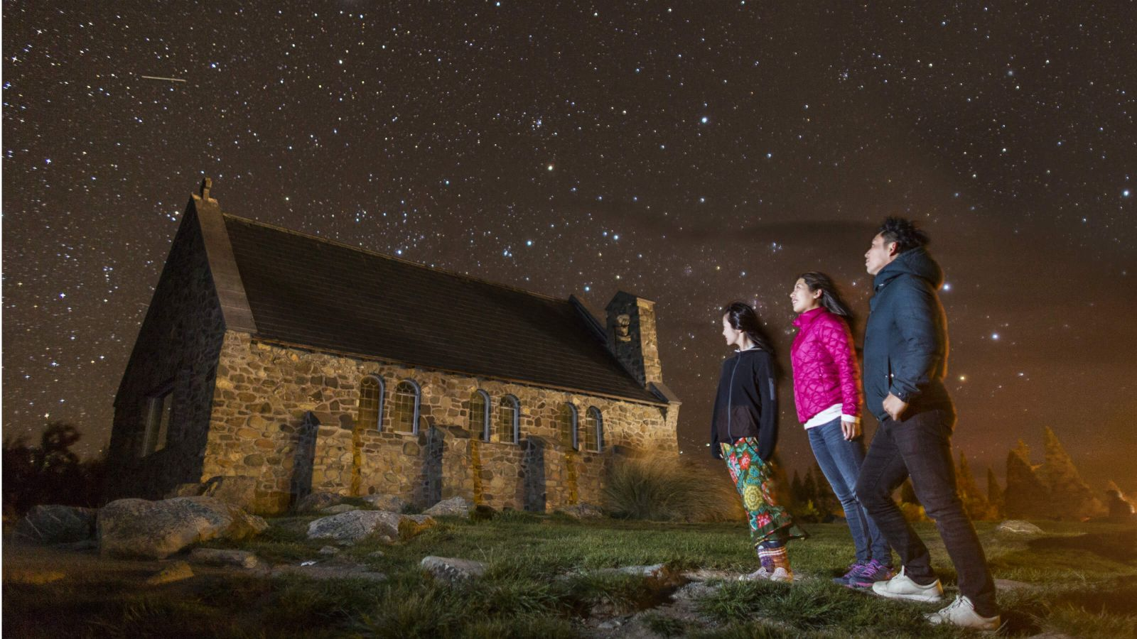 Image of three tourists stargazing at Church of the Good Shepard,Lake Tekapo, Canterbury