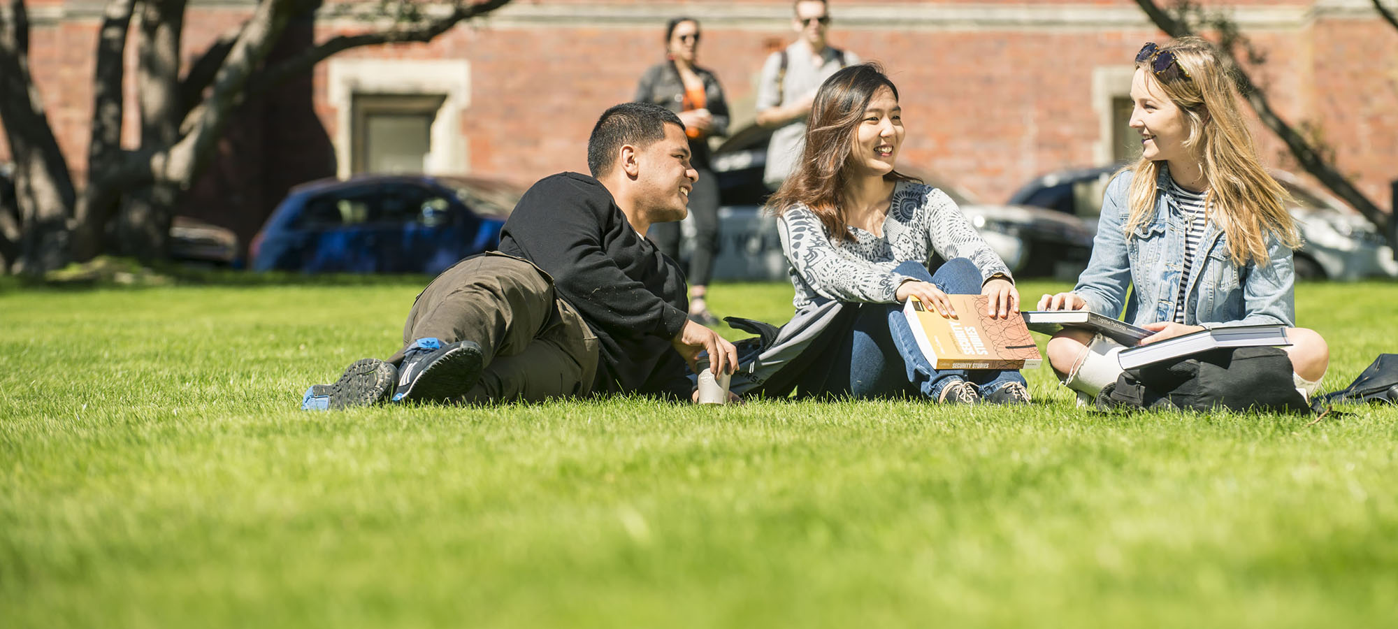 Three students study together on the grass outside the University's Hunter building.