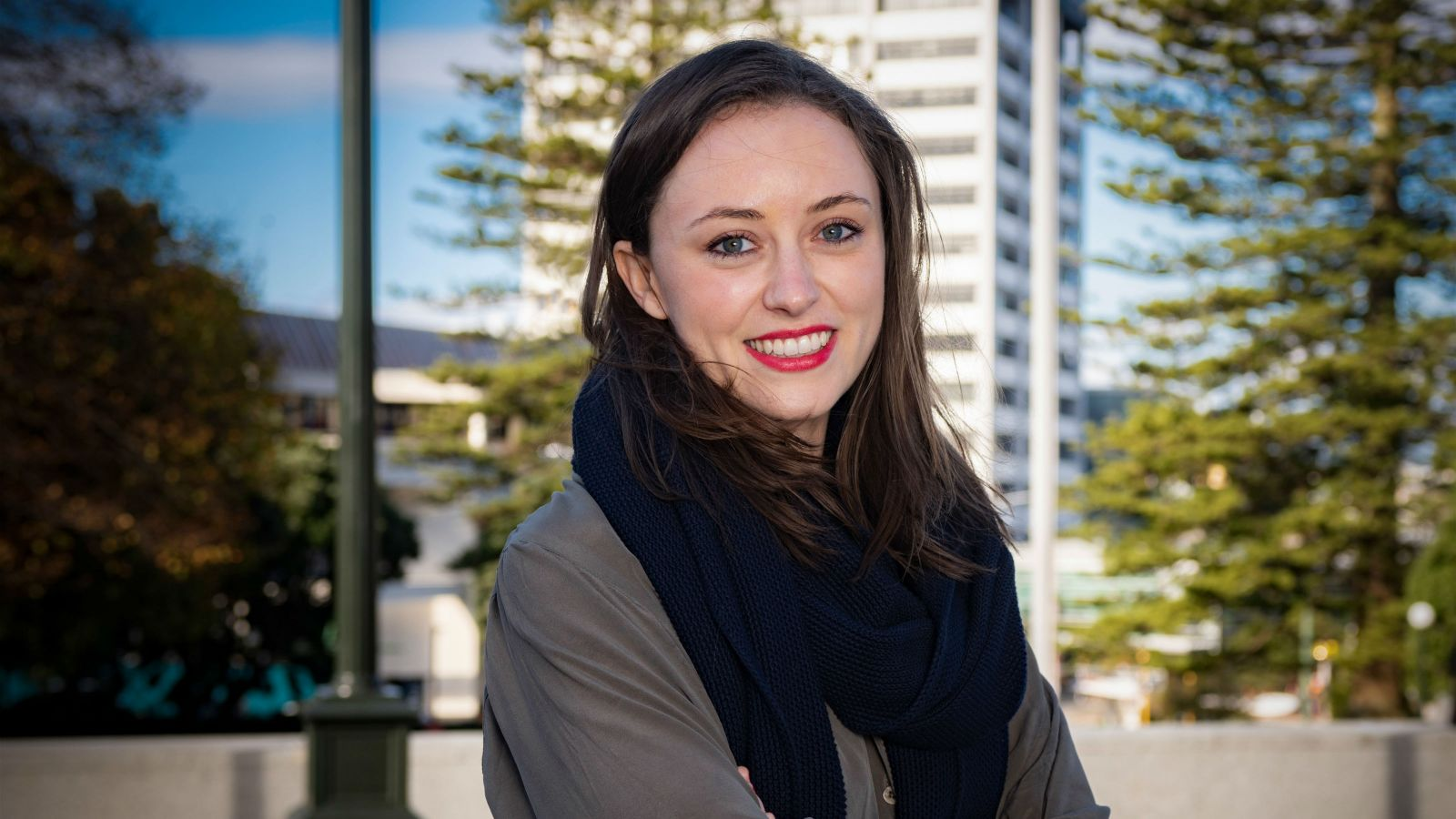Kell Howson, wearing a dark grey shirt and black scarf, stands with her arms crossed in Wellington city. Behind her is the blurred outline of a high rise building and trees.