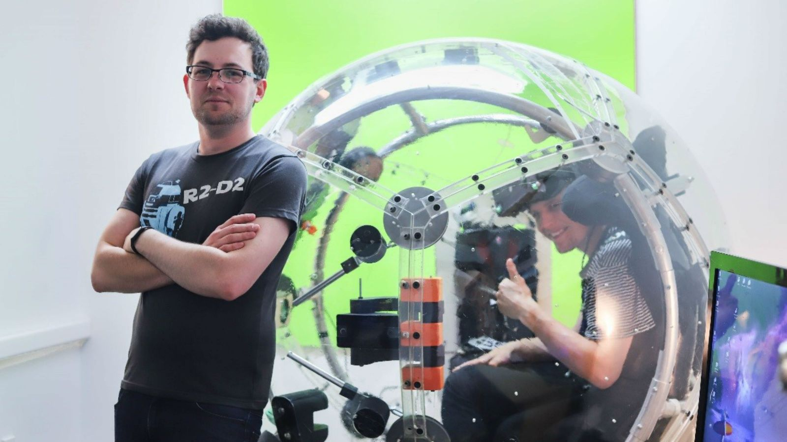 Terry Miller stands beside the immersive VR ball he developed