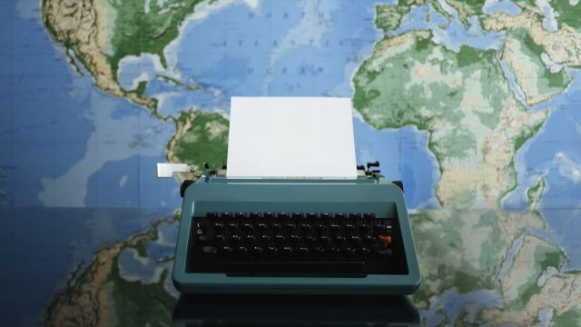 A typewriter sits in front a a world map