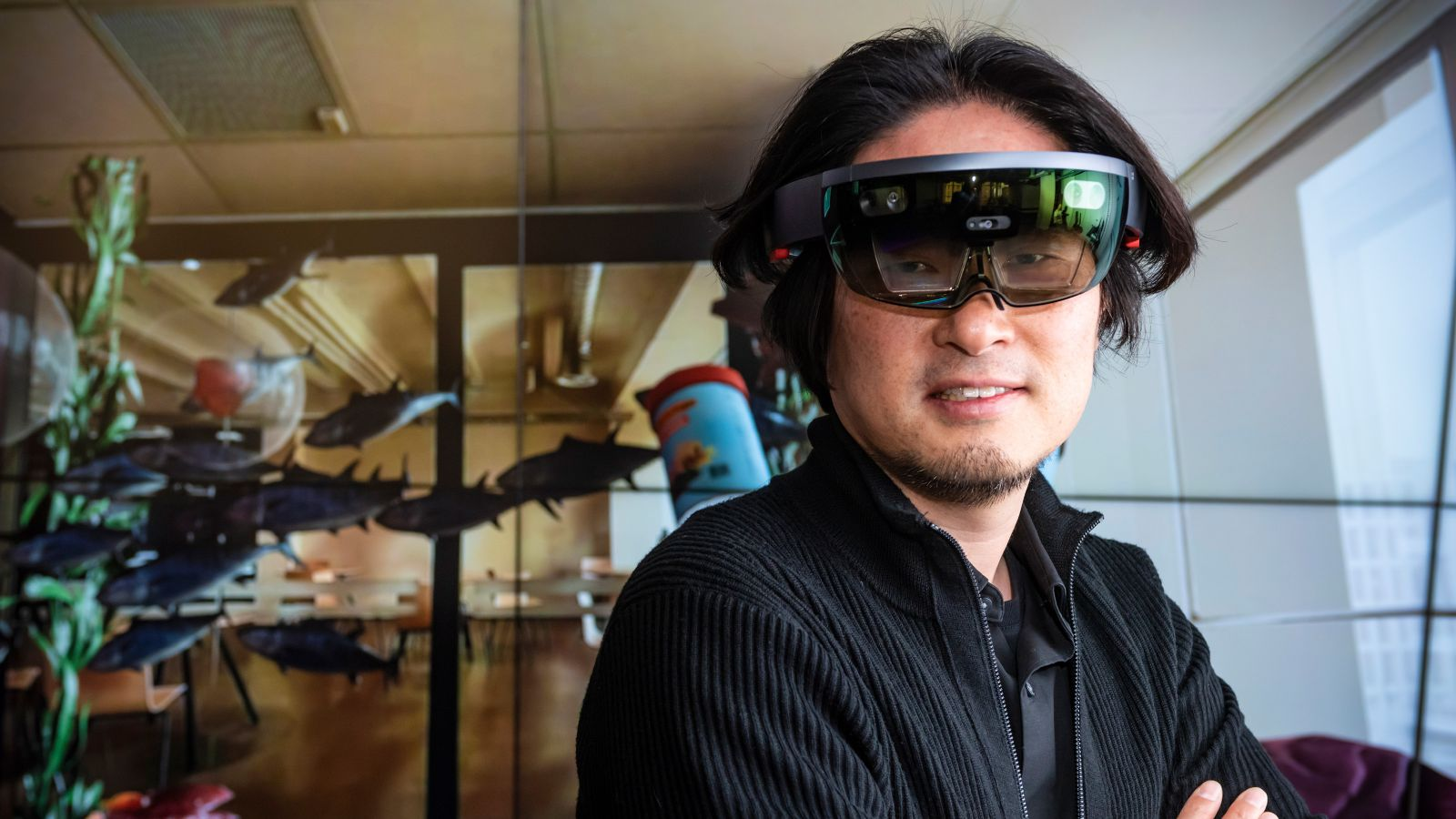Associate Professor Taehyun Rhee stands in a room wearing a virtual reality headset. Animated fish are floating through the air around him.