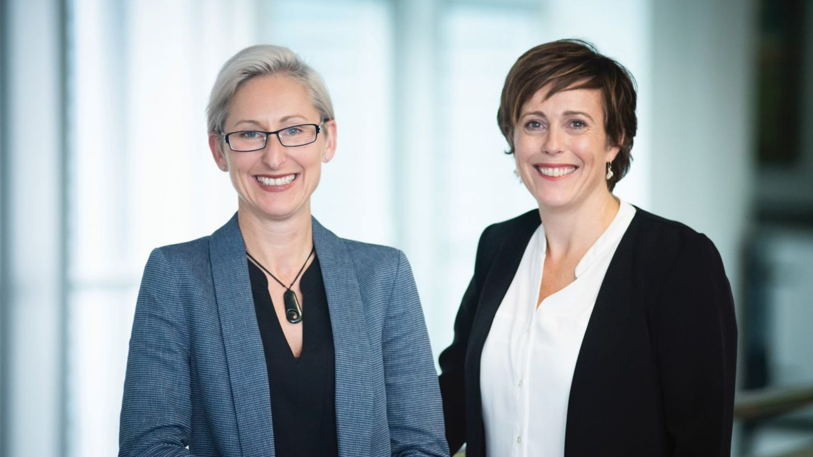 Caz Helen and Helen Rook are standing side by side, in professional atire, infront of a white background.