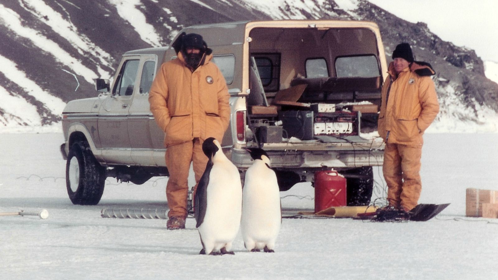 Two men in jumpsuits in Antarctica with penguins in foreground.