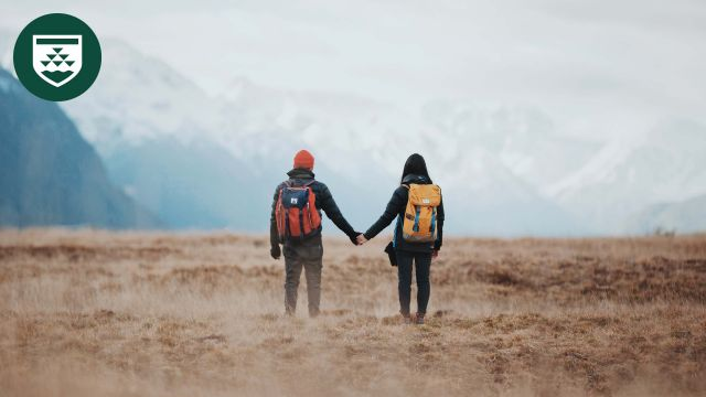 Two people hold hands in an empty field with mountains in the background.