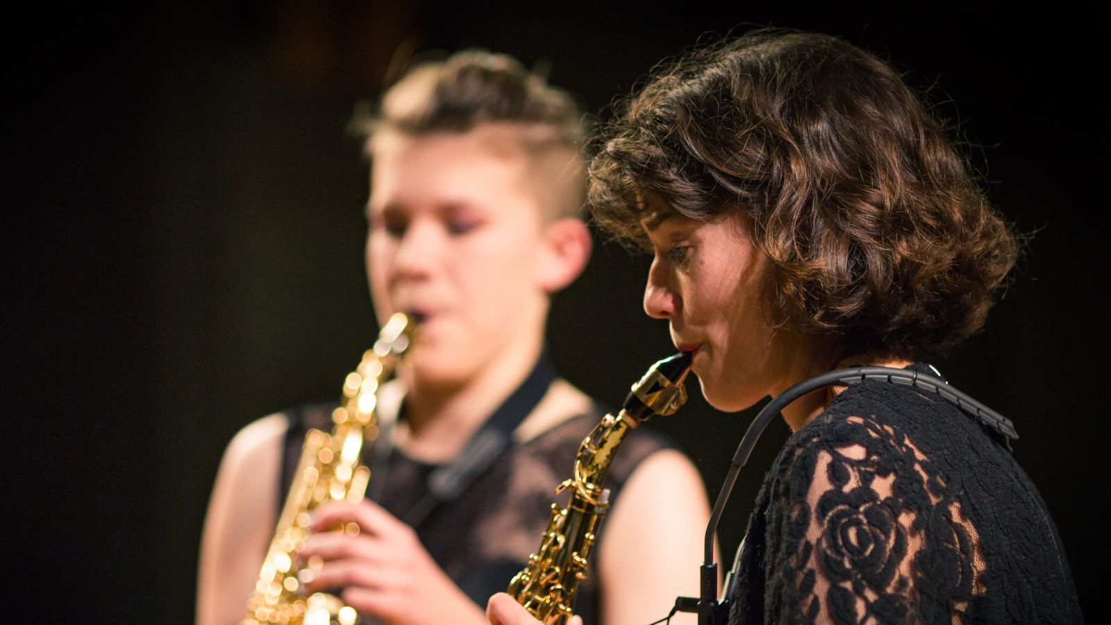 Two musicians playing saxophones
