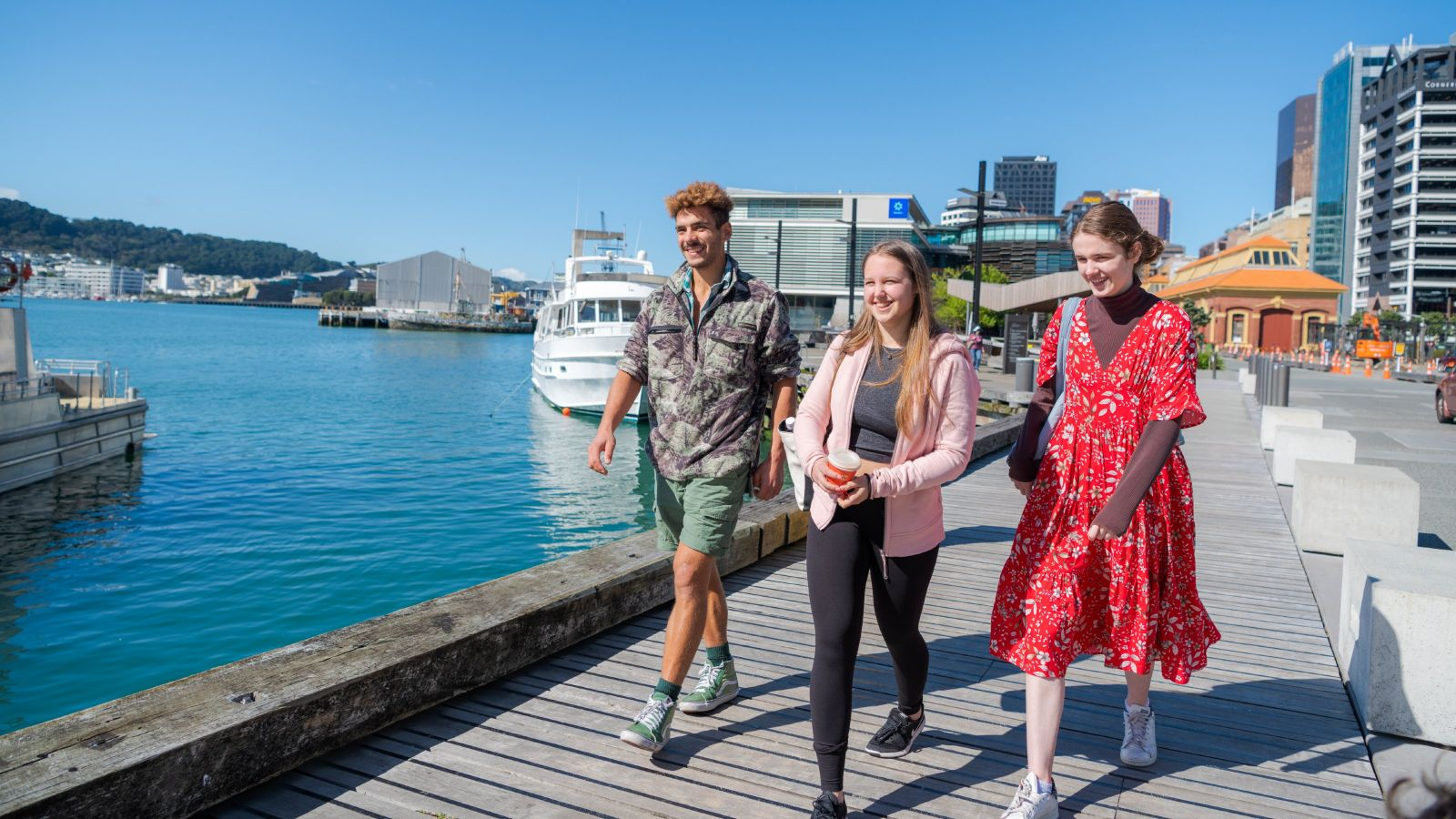 Three students walking together on the waterfront, by sunny weather.