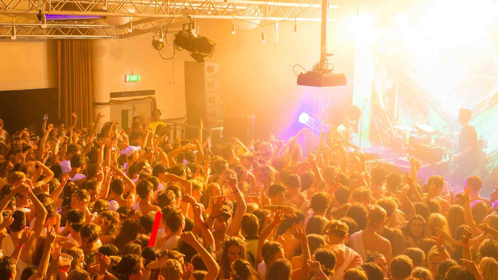A crowd at a music venue with hands in the air