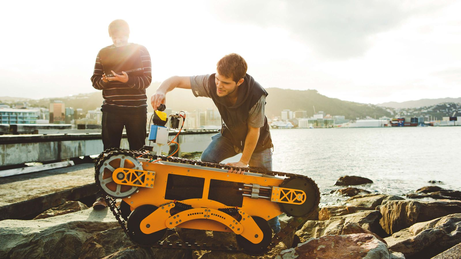 Two students work on an orange remotely operated vehicle that has large tracks – Wellington is in the background.