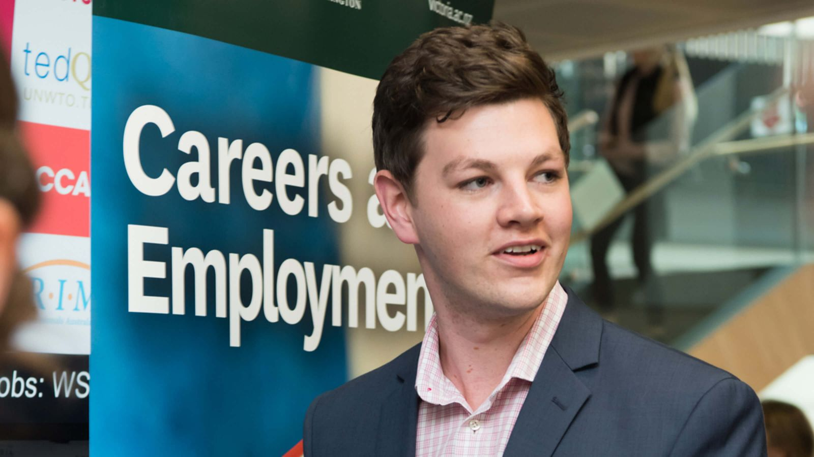 A young male Pakeha business student wearing a suit jacket and pink shirt at a Careers expo