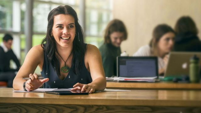 Bachelor of Commerce student, Brittany Baltus, is sitting with other students in an open plan study area at Rutherford House, Pipitea campus.