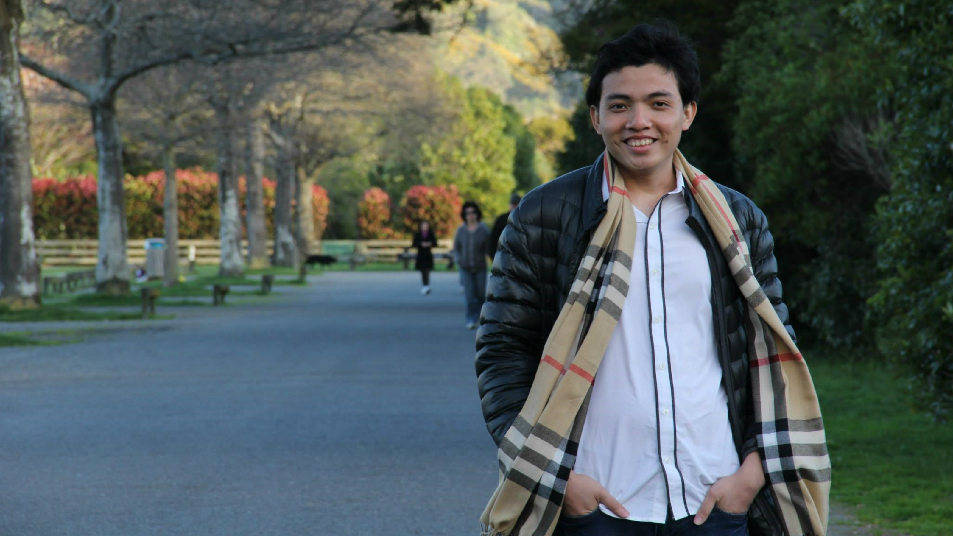 Wearing a white shirt, black jacket, and plaid scarf, Tran The Trung stands with his hands in his pockets on a park pathway shaded by autumnal coloured trees.