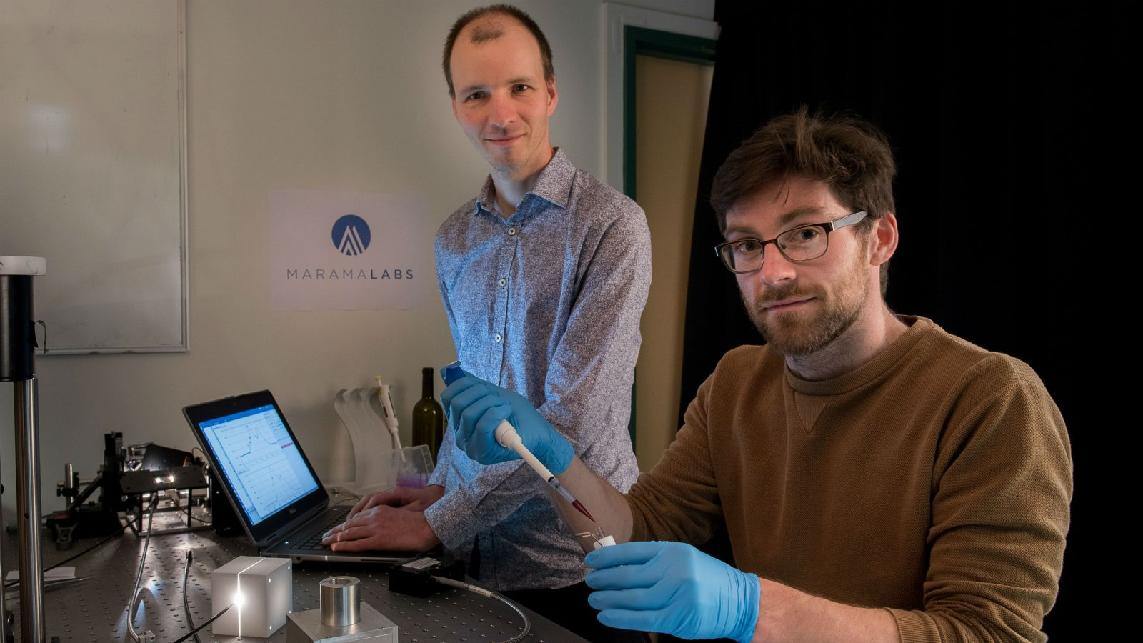 Mattias Meyer stands at a laptop with Brendan Darby sitting at the desk. Brendan wears blue gloves and is holding lab equipment. MaramaLabs and the logo are in the background.