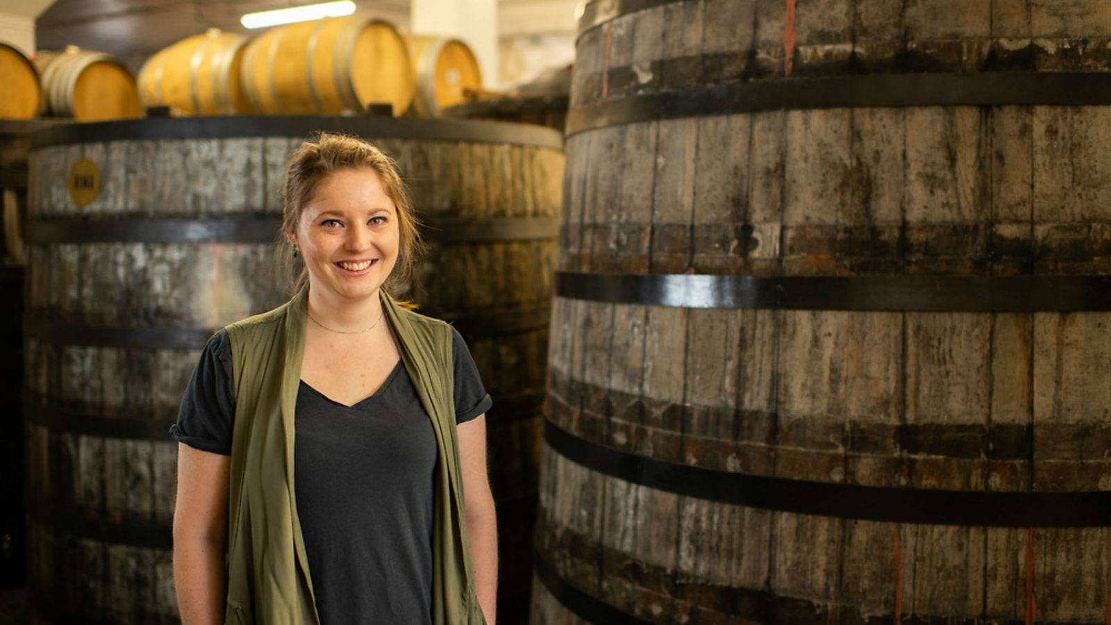 Alyssa, wearing a black top and green sleeveless cardigan, stands in front of large wooden barrels.