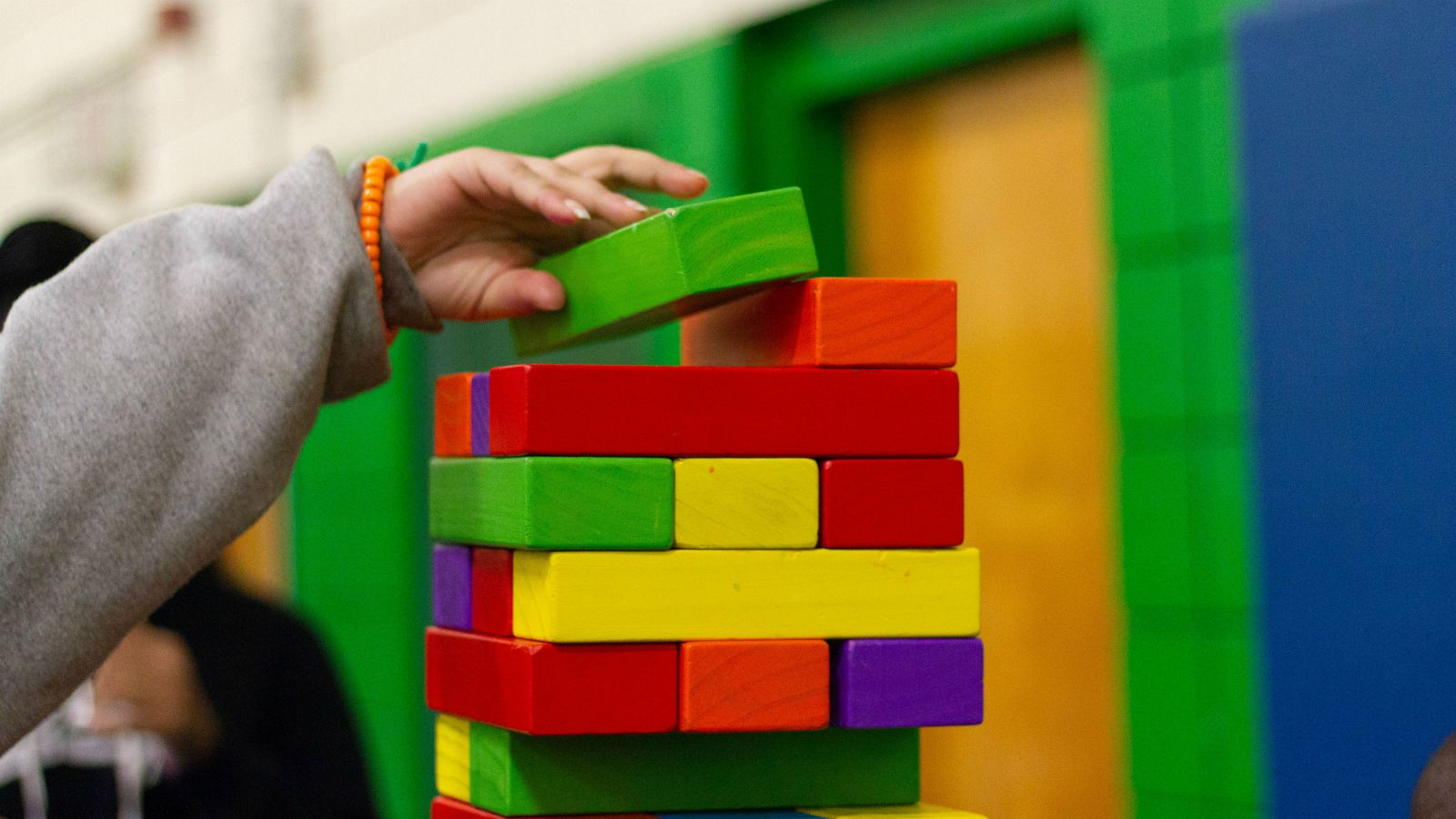 A close-up image of a hand placing a green block on an oversized Jenga set.