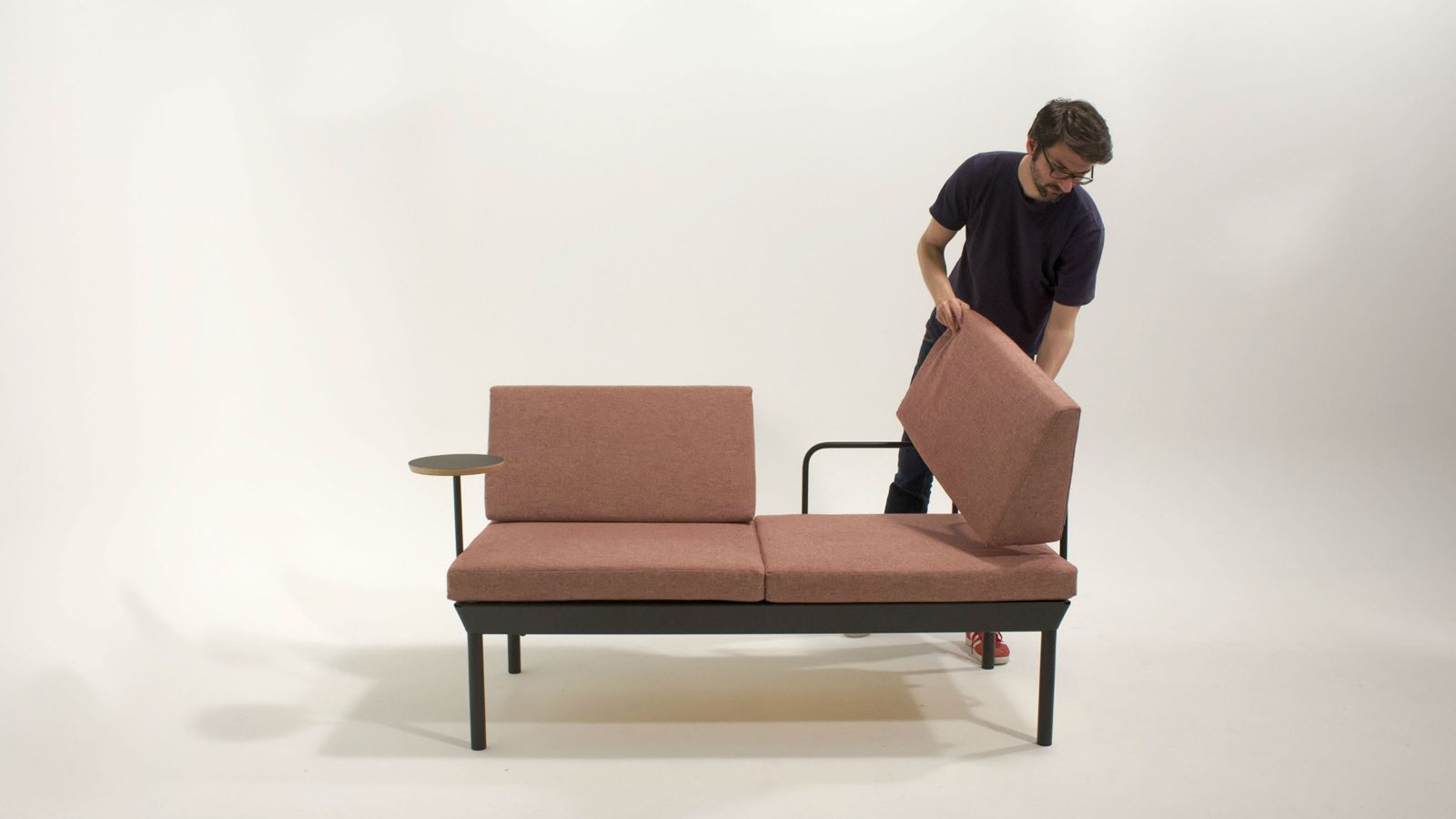 Steven Almond places a cushion on the 30 year sofa he designed for his Master's research.