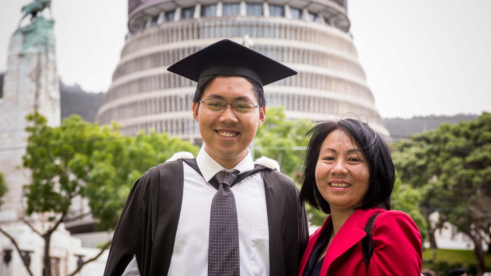 Male student with family member in graduation gown in front of parliament Beehive.