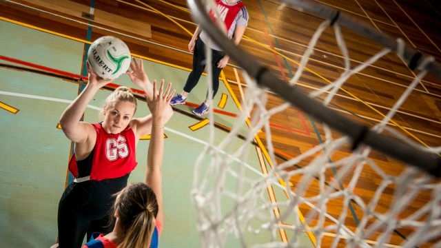 Female netball player about to shoot the ball into the netball hoop.