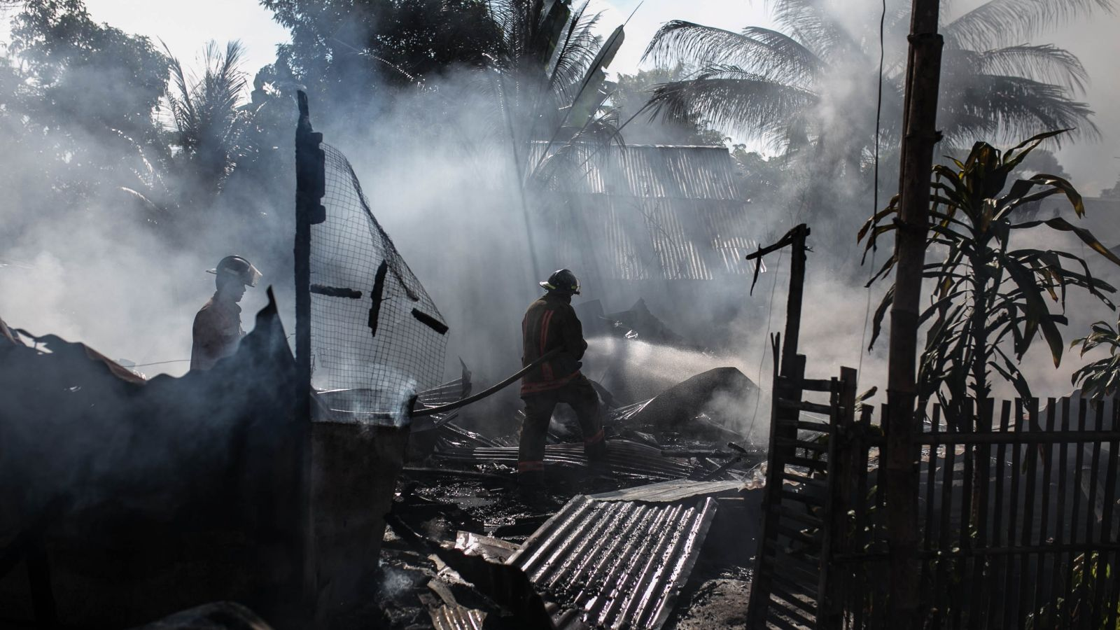 Silhouettes of two firefighters in helmets spraying water on burnt tropical shanty house with corrugated roof iron in foreground. Aftermath of fire in Philippines. Photo: Denniz Futalan, Pexels.