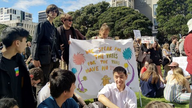 """Students gathered for a protest, one holds a sign that reads, """"We speak for the tree, for the trees have no tongue""""."""