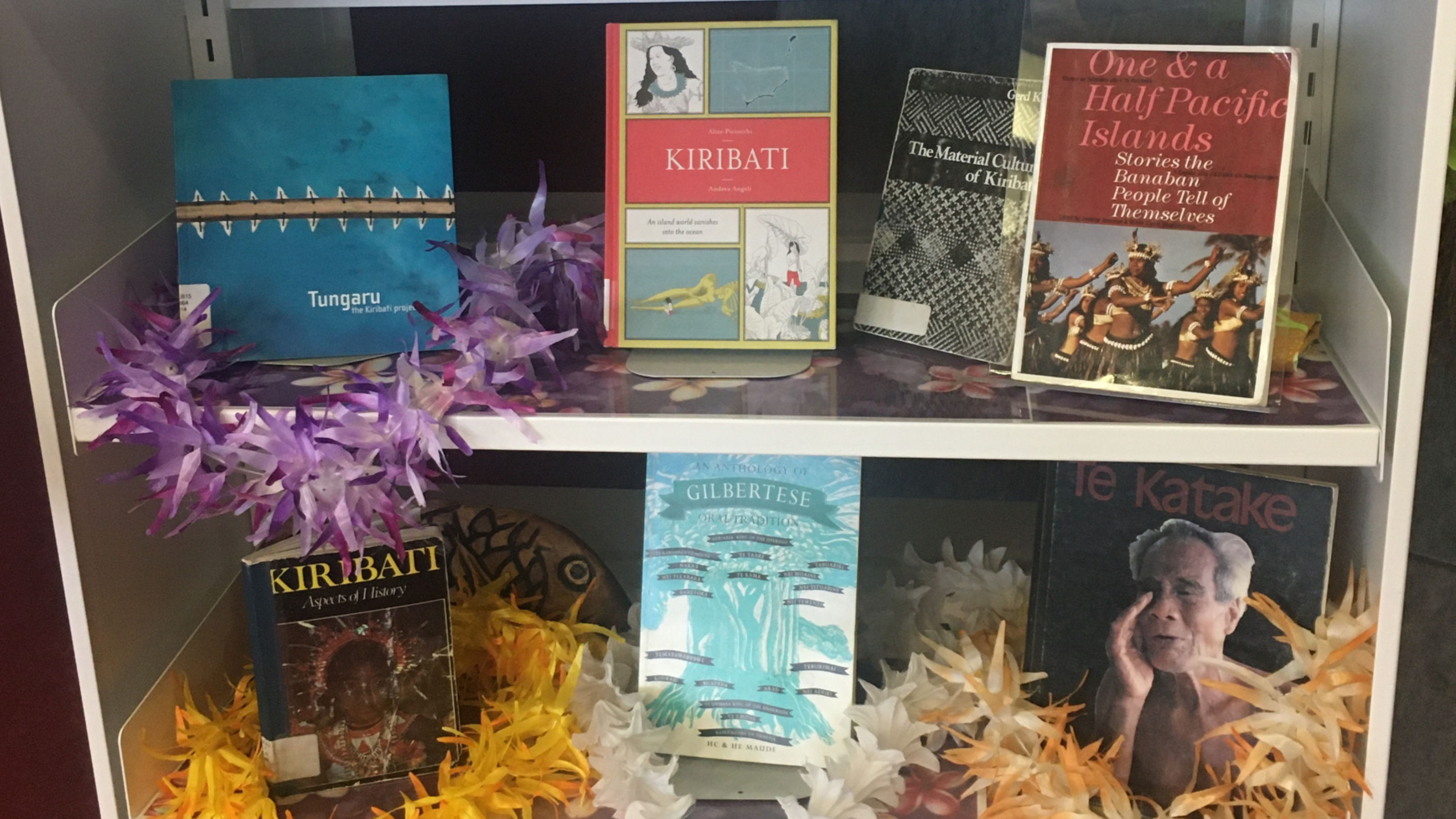 Seven books about Kiribati presented on library shelves surrounded by purple, yellow, and white garlands.