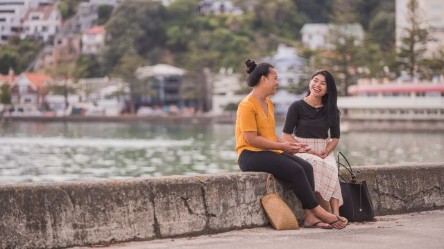 Two students sitting by the sea in Oriental bay.