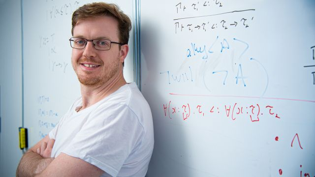 Smiling man stands in front of a whiteboard showing mathematical equations.