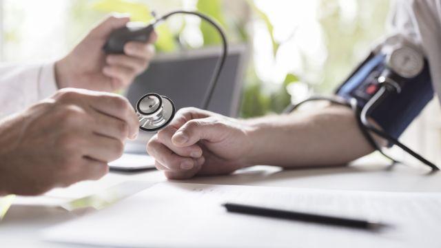 A GP measures a patient's blood pressure.
