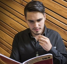 Young bearded man looking down at notebook with diagonal wooden slats on background wall