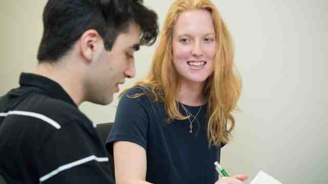 Lucy Woods, a young woman with long red hair, writing notes for a young male university student.
