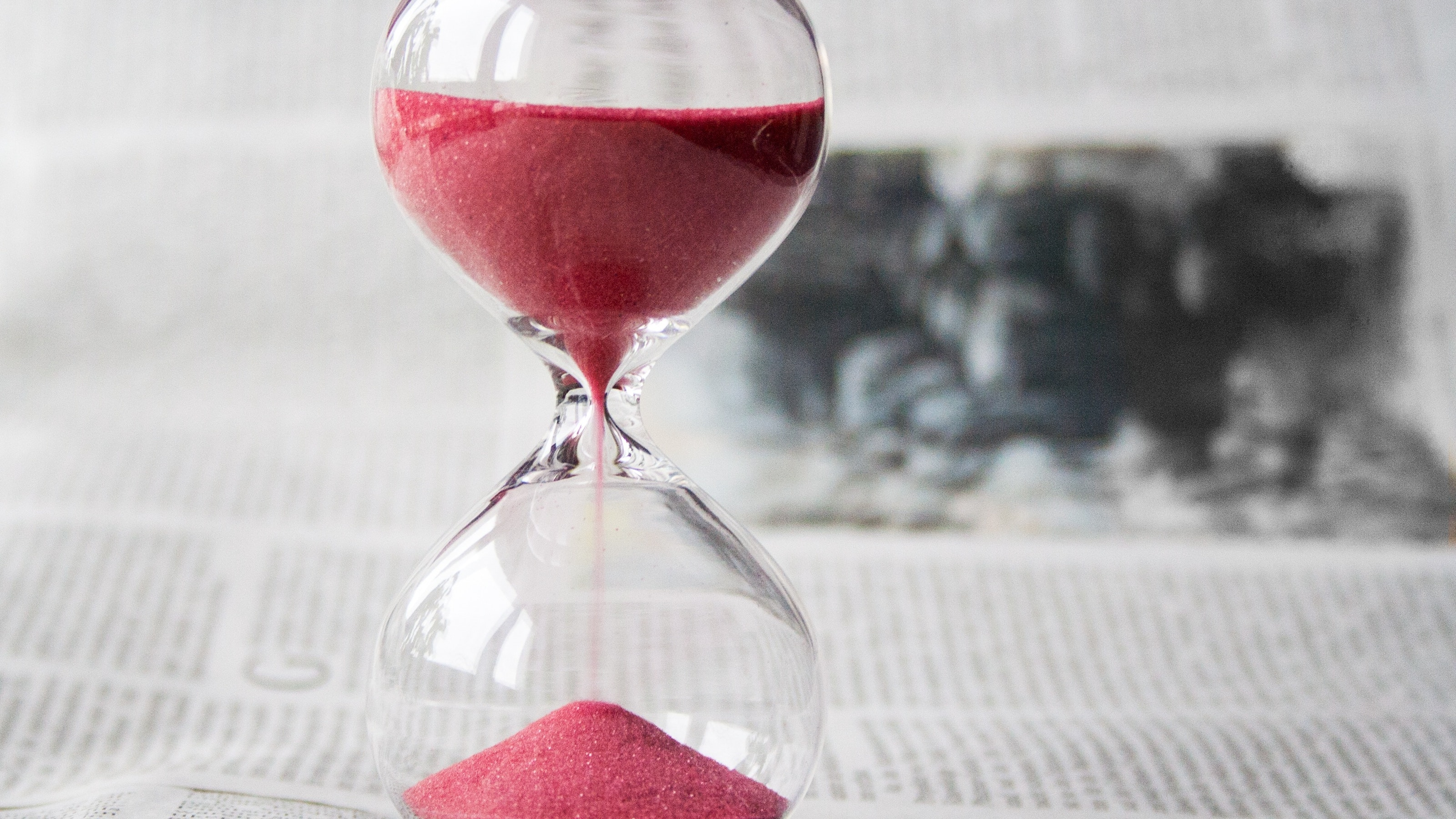 Close up of an hourglass with red sand inside it.