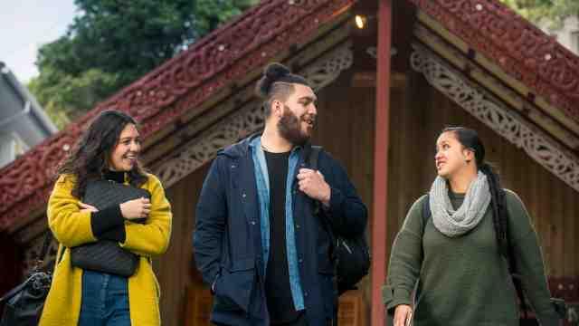 Three Māori students stand in front of Te Herenga Waka Marae at Victoria University's Kelburn campus.