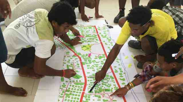A group of youth from Betio, Kiribati sit on the floor around an architectural plan of their city, writing notes and planning their community centre.