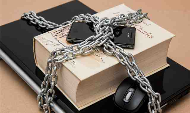 A book, cellphone and laptop chained together