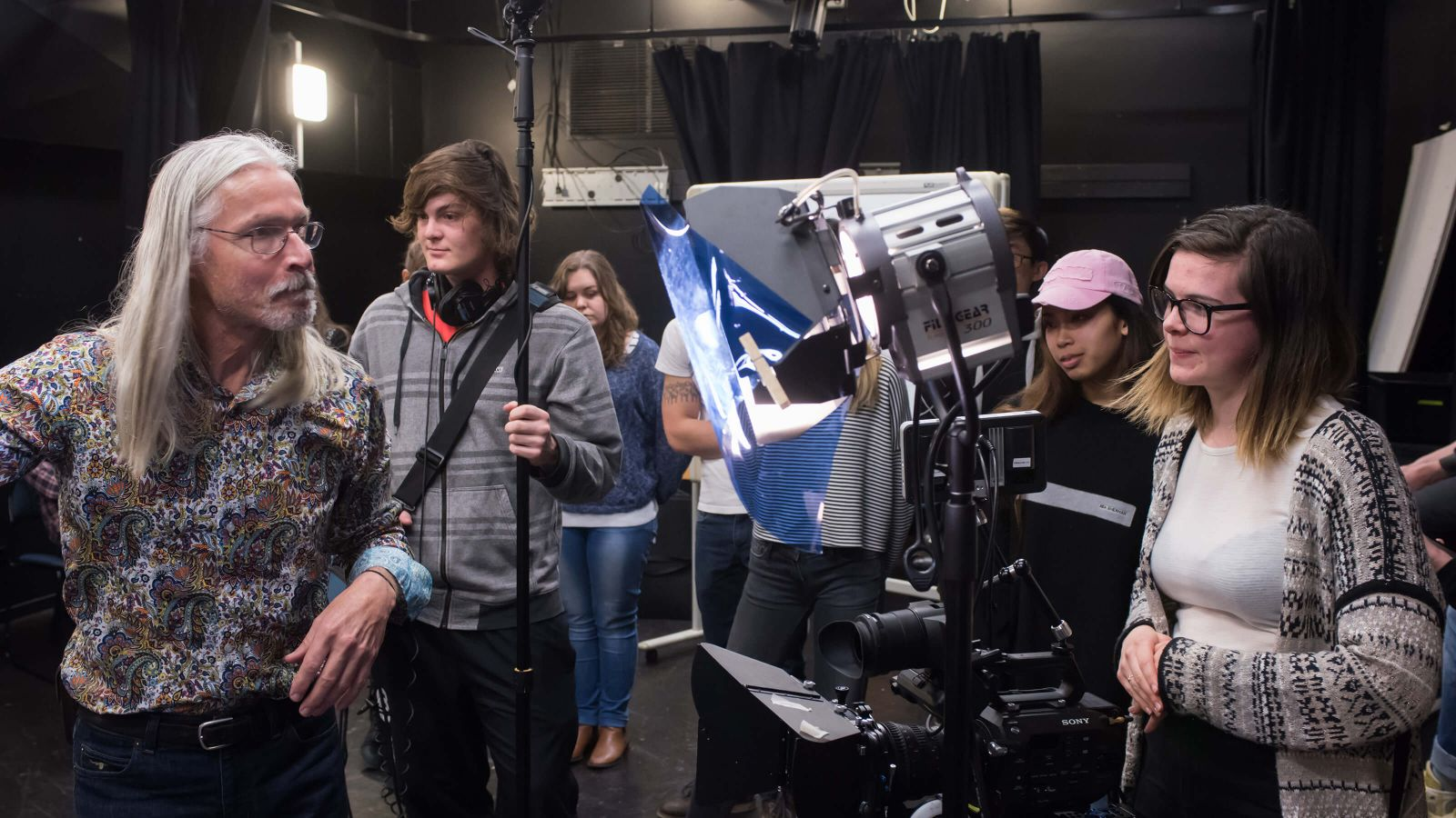 A film crew by a camera and lighting.