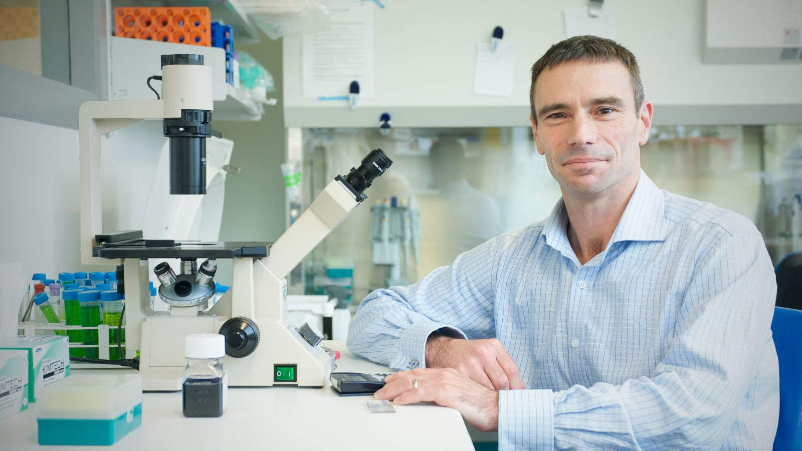 Photograph of Gavin Painter sitting with a microscope in a lab.