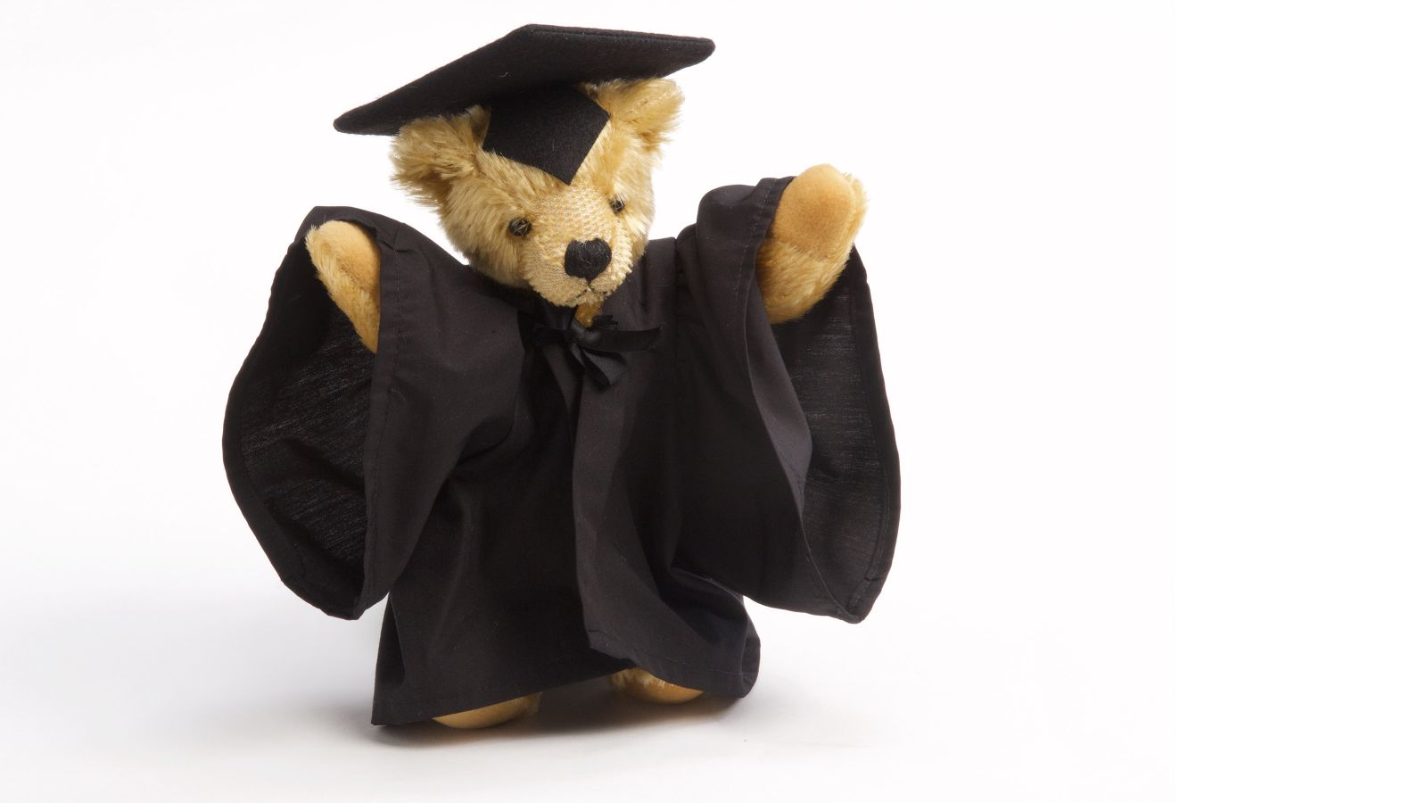 A small teddy bear wearing a graduation gown and hat.