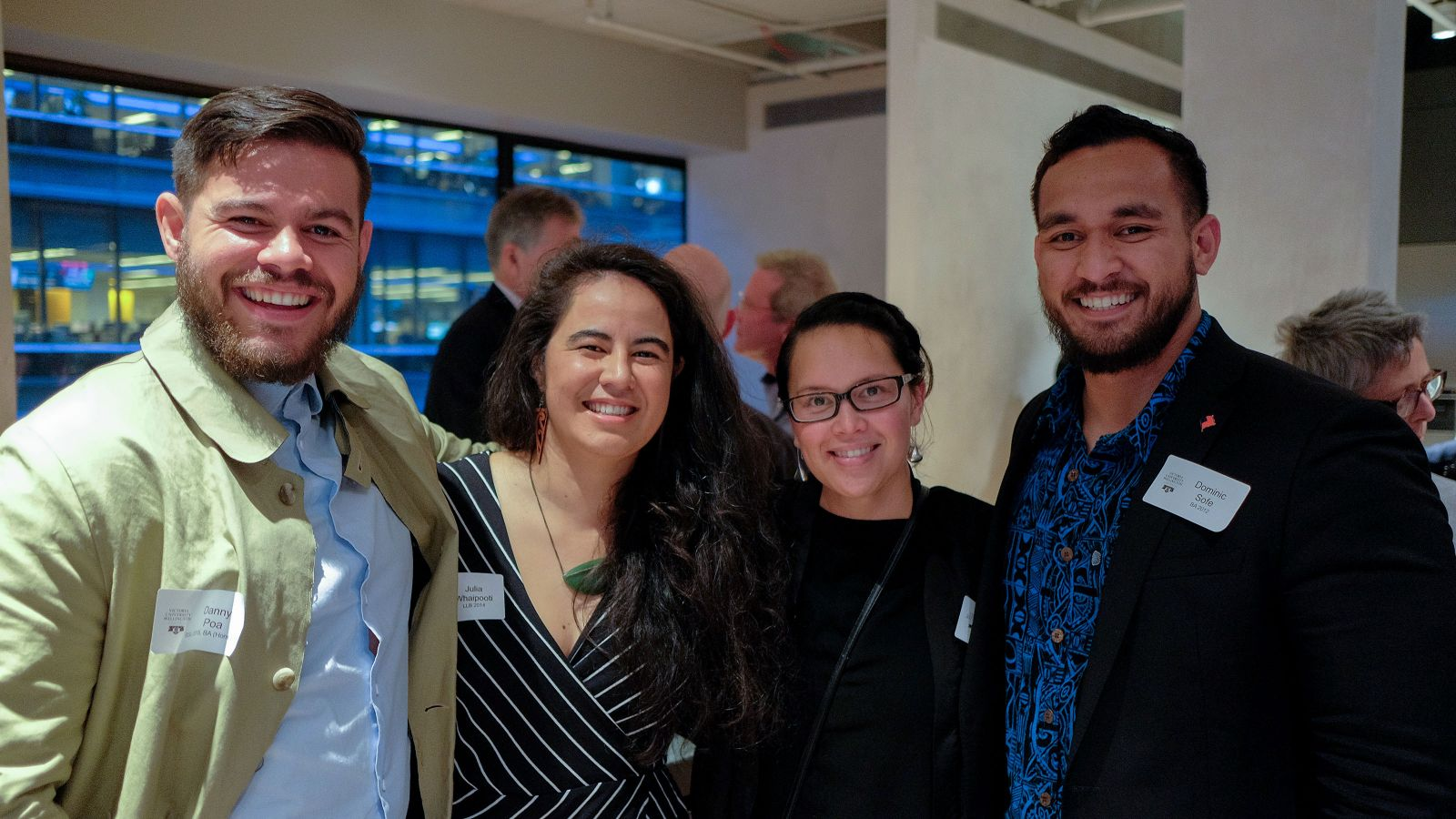 Four alumni—two men and two women—smile for the camera at an alumni event.