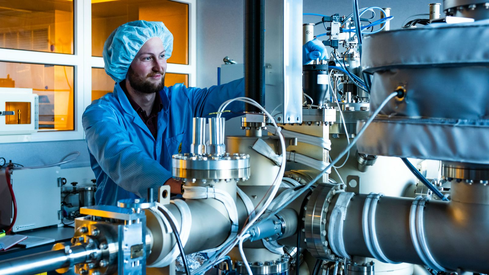 Tane, wearing a blue lab coat and a hair covering, looks at physics equipment in a small lab.