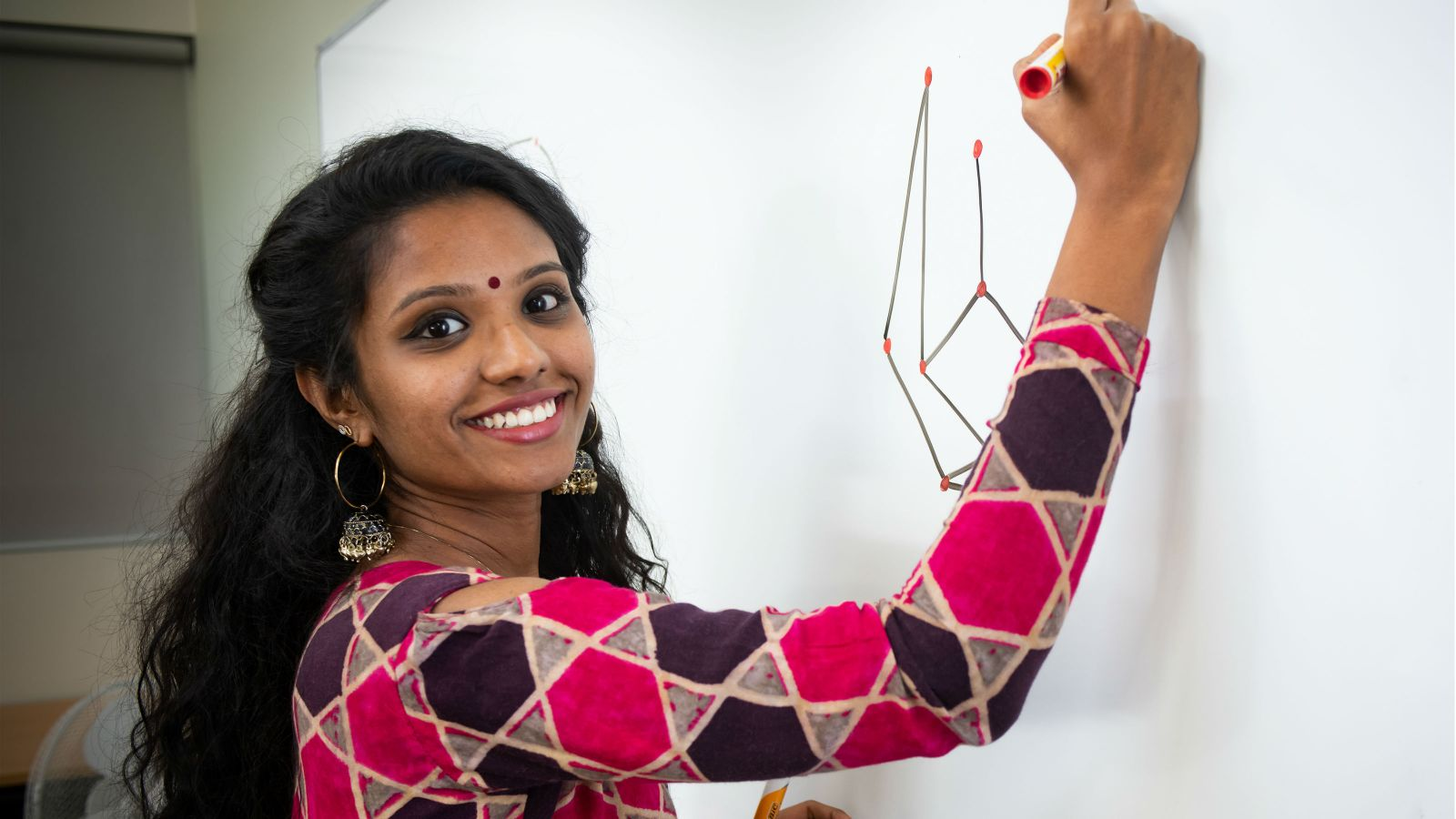 Meenu draws symbols on a white board and looks towards the camera with a smile.