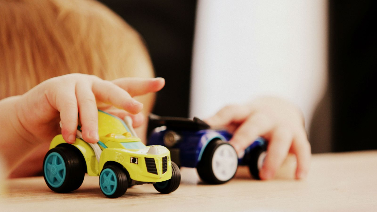 A child plays with toy cars.