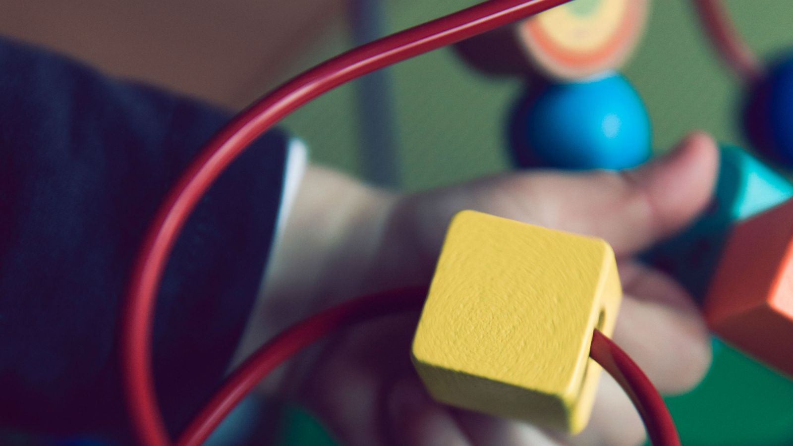 The hand of a small child moves a yellow cube on a read wire.