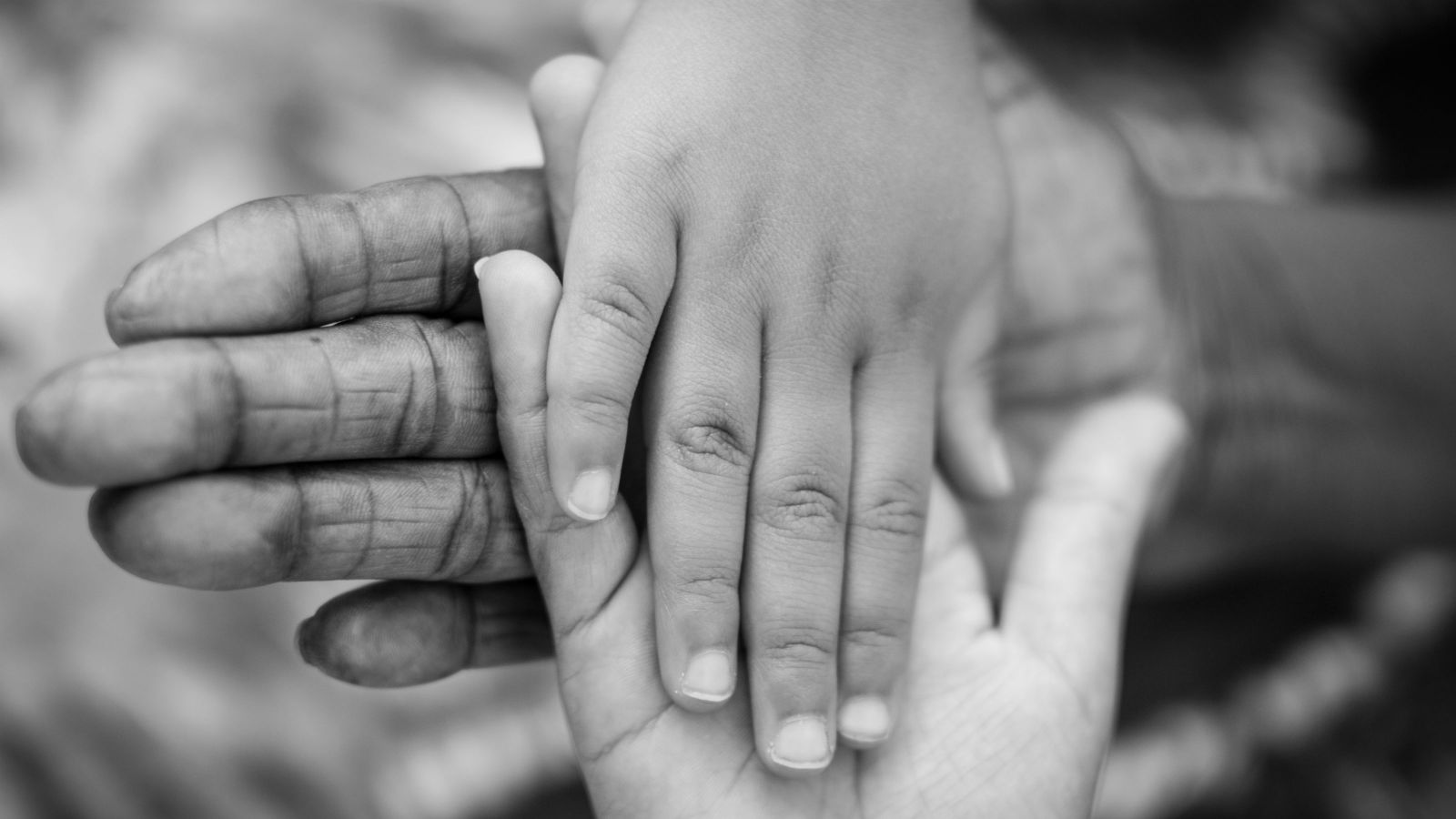 Two adult hands and a child's hand together