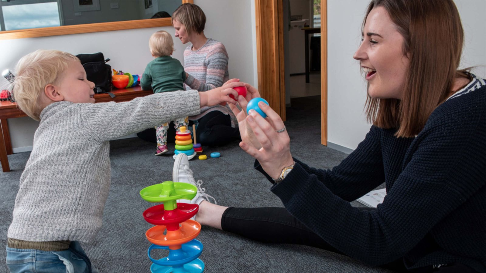 Two women playing with two toddlers and colourful children's toys.